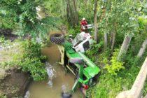 Un tractor s-a răsturnat într-un pârâu, șoferul a rămas blocat în cabină
